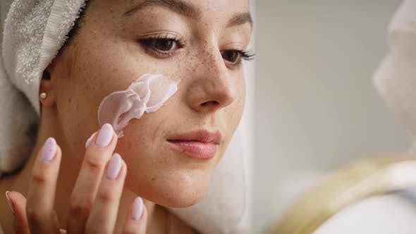 Close up video of beautiful woman applying facial mask. Shot with RED helium camera in 8K.