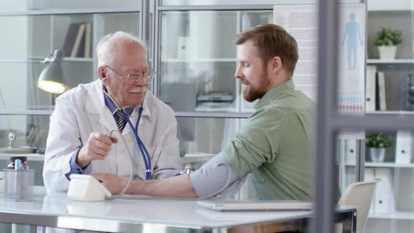 Thumbnail for Senior Doctor Testing Blood Pressure of Young Male Patient