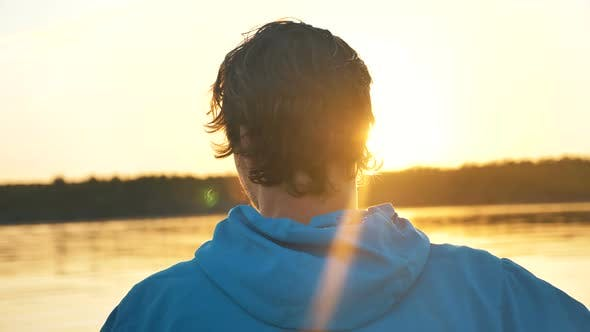 Thumbnail for Portrait of Man Turns Head Around Against Background Sunset on Lake, Outdoor Activities Alone