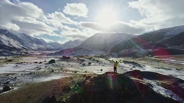 Young Hiker Reaching The Top Outstretched Arms Success Pose At Sunset In Snowy Mountain Range Aerial