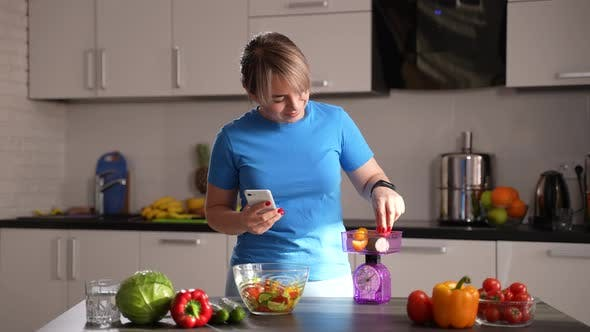 Slimming Woman Weighing Vegetables in Kitchen