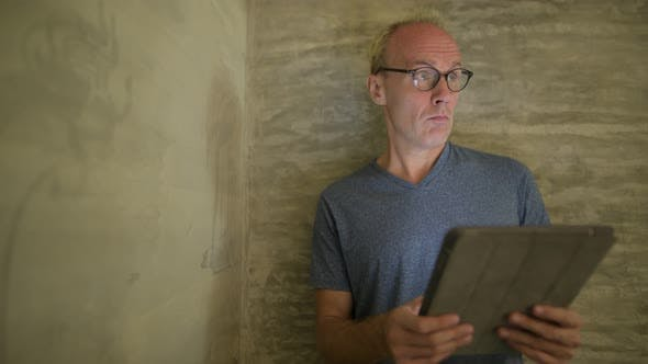 Mature Scandinavian Man Using Digital Tablet at Home