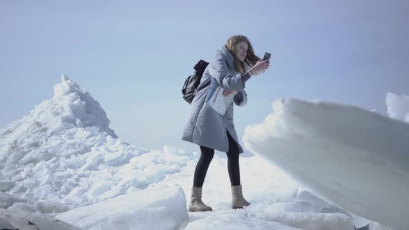 Thumbnail for Young Blond Pretty Woman in Warm Jacket Walking on the Glacier with the Map in Hands, Holding Her