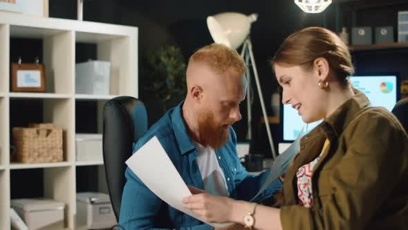Thumbnail for Amazed Business Couple Checking Documents in Stylish Interior.