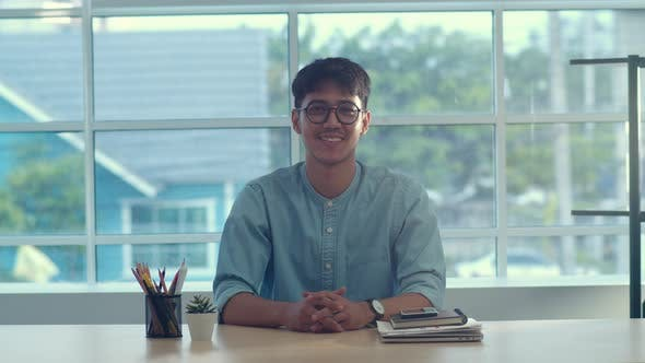 Young Asian creative man smiling in office.
