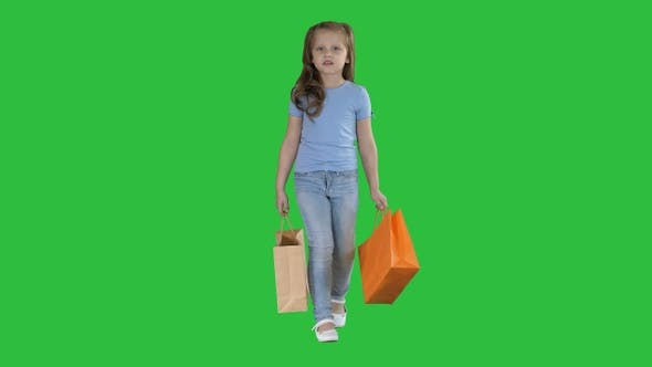 Thumbnail for Little girl with shopping bags walking on a Green Screen