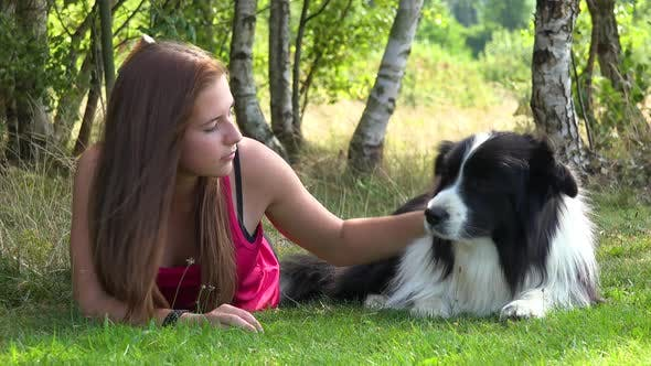 A Woman and a Border Collie Lie on Grass in a Meadow, the Woman Occasionally Pets the Dog and Looks