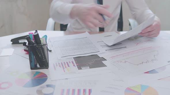 Thumbnail for Geschäftsmann arbeitet mit Diagrammen im Büro am Tisch und unterschreibt Dokumente