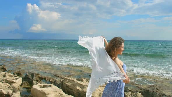 Cover Image for Young Attractive Woman Holding White Scarf in the Wind on Seashore, Freedom