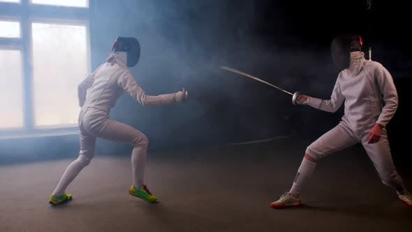 Cover Image for Two Young Women Fencers Having a Dynamic Training Duel in the Smoky Studio