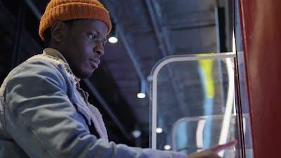 Smiling Black Man Chooses Burgers on Interactive Display