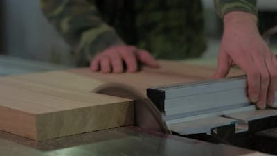 Worker in Camouflage Sawing Wood on The Machine