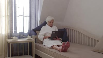Beautiful Elderly Lady with Laptop Chatting Online in Hotel