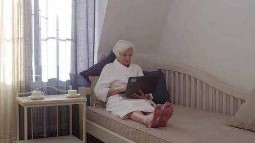 Schöne ältere Dame mit Laptop Chatten Online im Hotel