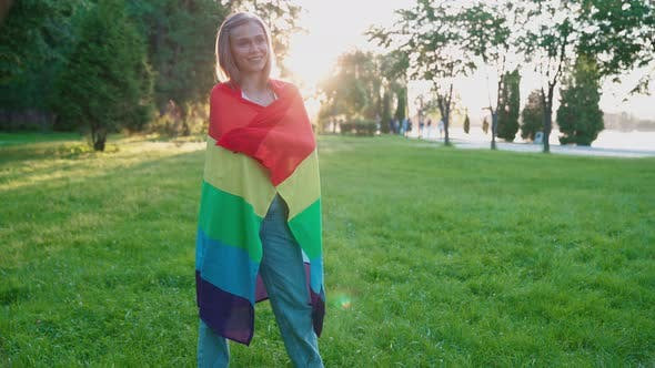 Thumbnail for Smiling Woman Holding Rainbow Flag Around Body.
