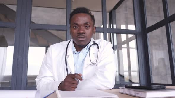 African Male Doctor Consulting Patient During Virtual Telemedicine Advice