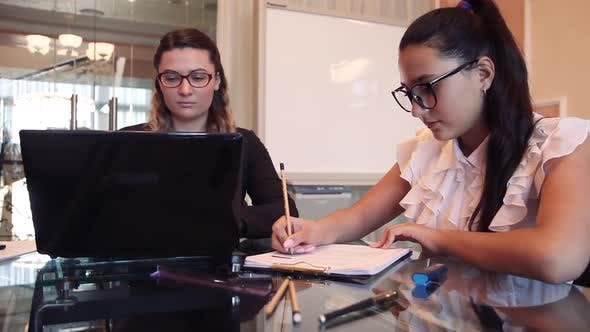 Two Business Women Working on a Business Project in an Office Sitting at a Table Using a Computer