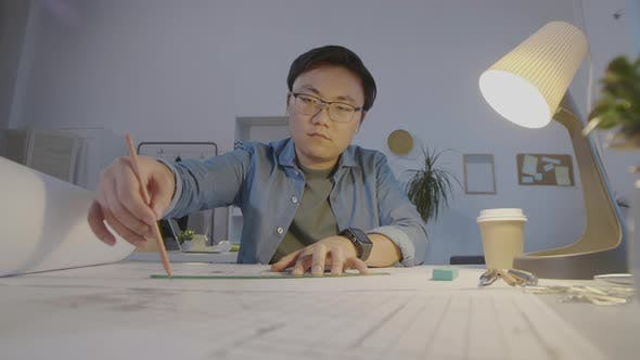 Thumbnail for Asian Architect Sitting at Desk and Drawing on Paper