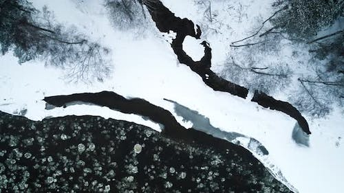 Icy River And Frozen Ground Surface Covered With Snow