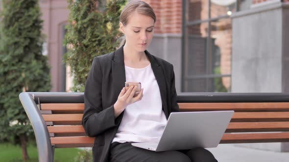 Cover Image for Young Businesswoman Using Smartphone and Laptop, Sitting on Bench