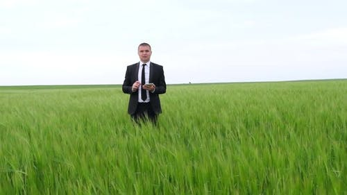 A farmer agronomist walks on a green field of wheat and checks the harvest.