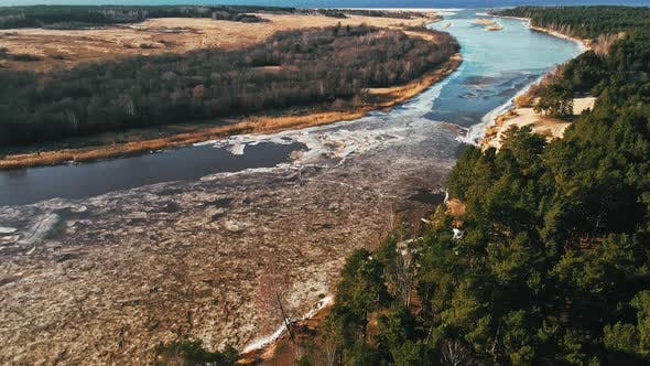 Melting Snow and Ice at River Joining Sea in Spring Aerial