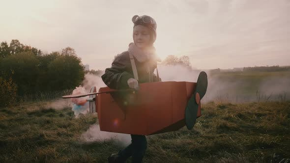 Thumbnail for Little Pilot Girl Running in Fun Cardboard Airplane with Color Smoke Behind on Amazing Autumn Sunset