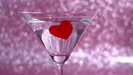 Coeur gommeur rouge s'enfonce dans un verre