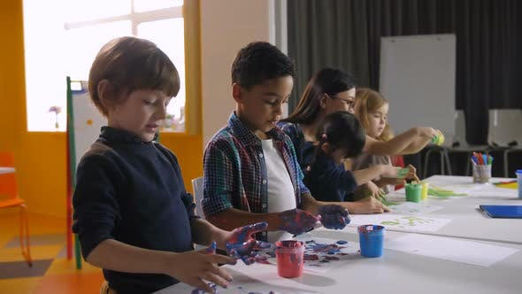 Diverse Children Hand Painting in Kindergarten
