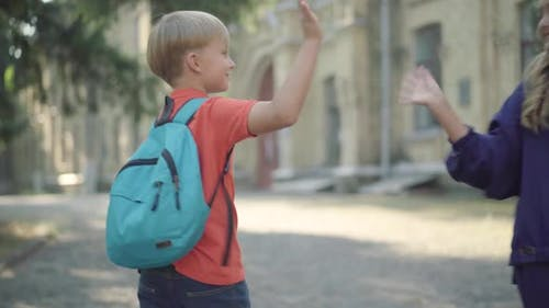 Camera Follows Little Blond Schoolboy Waving To Friends and Marching To School in Sunlight. Happy
