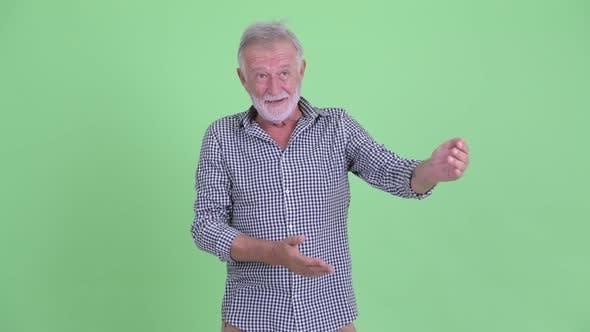 Thumbnail for Happy Senior Bearded Man Presenting Something