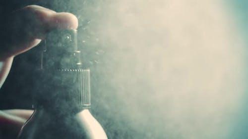 Spraying Water or Perfume on Dark Background