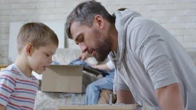 Boy Helping Dad to Arrange Screws