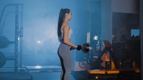 Mädchen hebt die Langhantel im Fitnessstudio