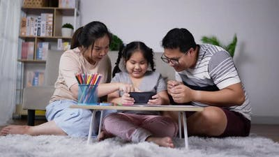 Happy family playing game online in mobile phone together
