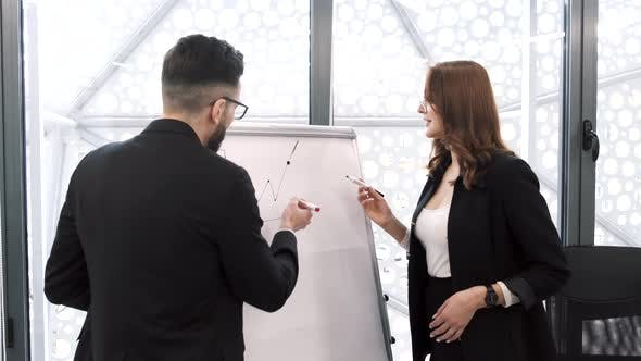 Woman Showing Statistics on Whiteboard to Coworker
