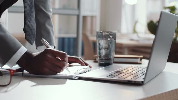 Thumbnail for Close Up of Afro-American Businessman Signing Document and Using Laptop