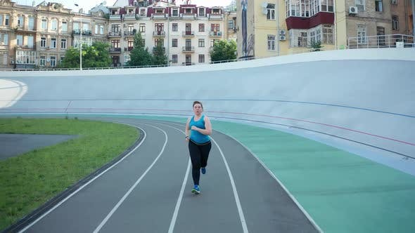 Thumbnail for Drone Shot of Plus Size Female Jogging at Stadium