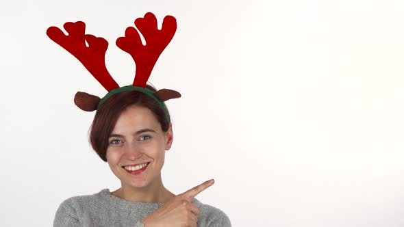 Thumbnail for Young Woman Wearing Reindeer Antlers Headband Pointing at the Copy Space