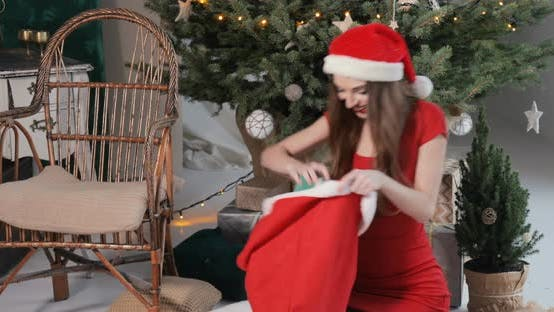 Thumbnail for Girl Takes Presents Out of Red Bag