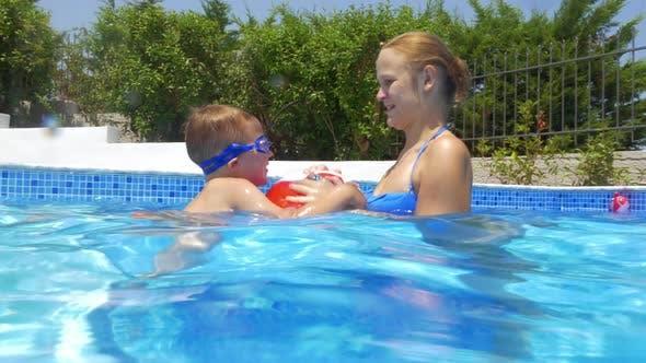 Frau, Junge und Ball im Schwimmbad