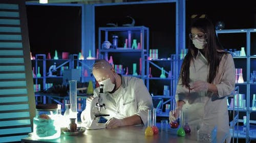 Male Chemist Looks at a Reaction Under a Microscope Pipette Solution Onto a Piece of Glass