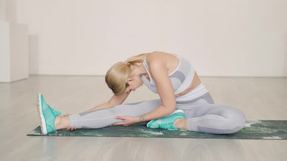 Female Athlete Sitting on Mat and Stretching