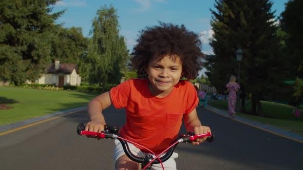 Thumbnail for Cute Mixed Race Boy Having Fun Riding Bike in Park