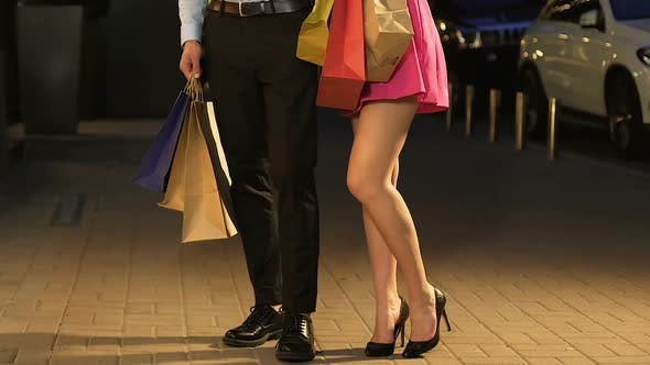 Cover Image for Girl in Short Dress Standing with Guy in Street, Shopping Day, only Legs in Shot