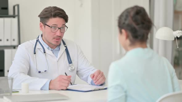 Middle Aged Male Doctor Discussing Patient, Medical Reports