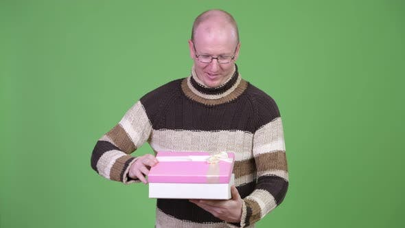 Thumbnail for Happy Mature Bald Man Looking Surprised While Opening Gift Box
