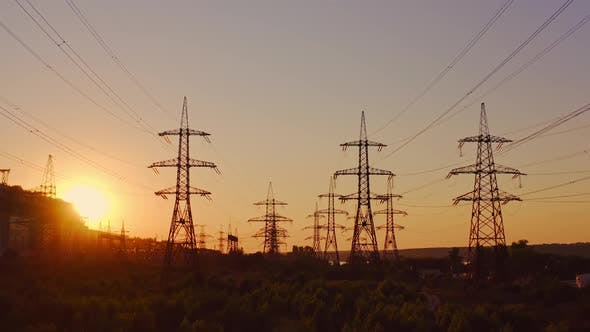 Wire electrical energy at sunset. High voltage electricity pole at sunset