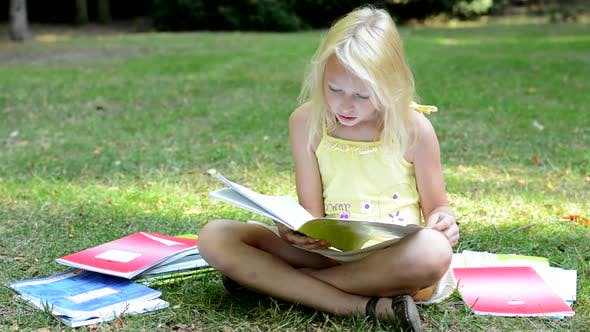 Thumbnail for Little Cute Smart Girl Sits in the Park Surrounded By Many Workbooks - She Read One and Study