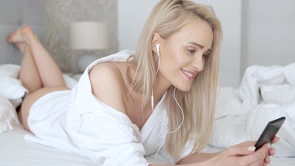 Thumbnail for Beautiful, Smiling Blond Woman Lying in White Bed and Using a Smartphone